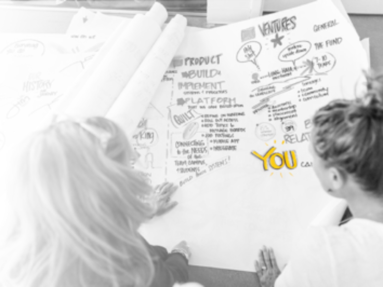 Two team members sketching graphic facilitation map on large paper
