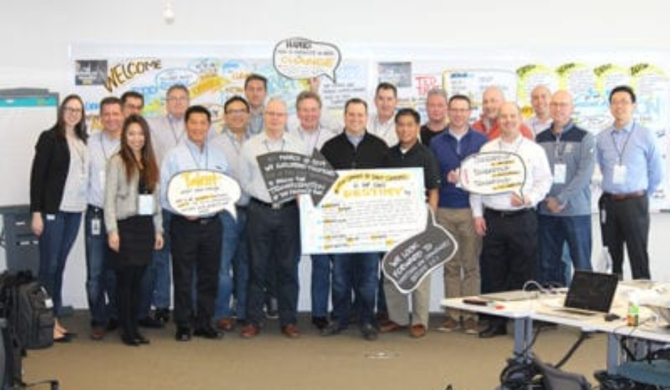 Corporate team after graphic facilitation session standing with their work from the day